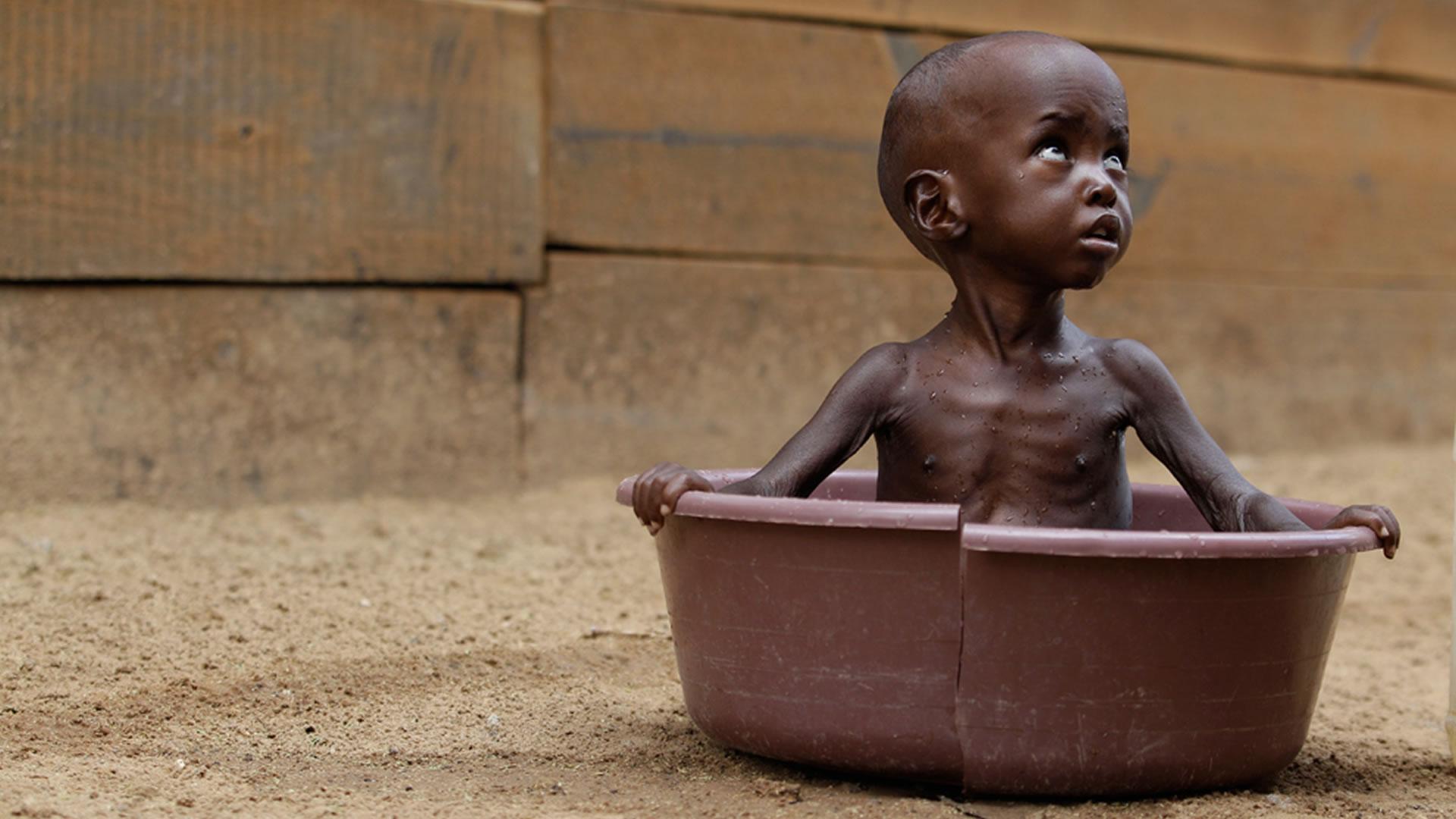 Hungry African boy sitting in empty broken bath tub